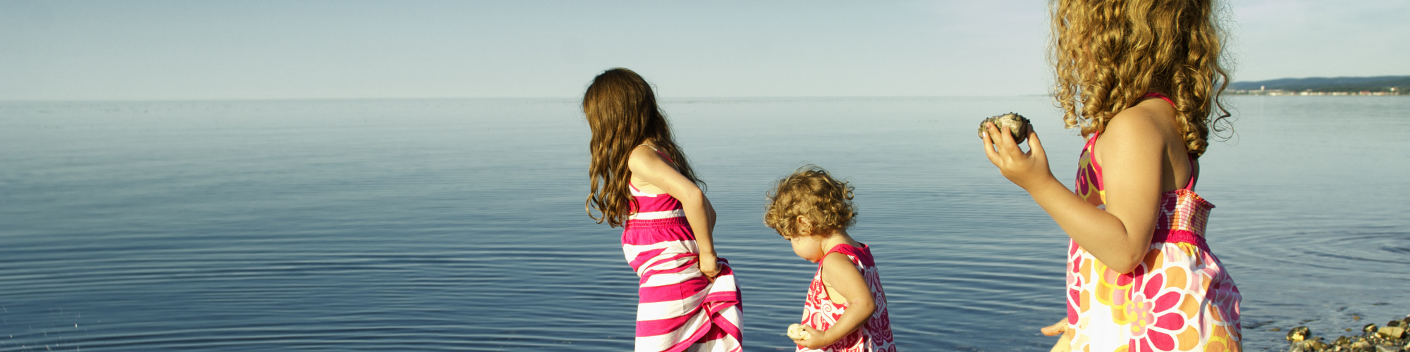 3 little girls playing on the beach, near the water