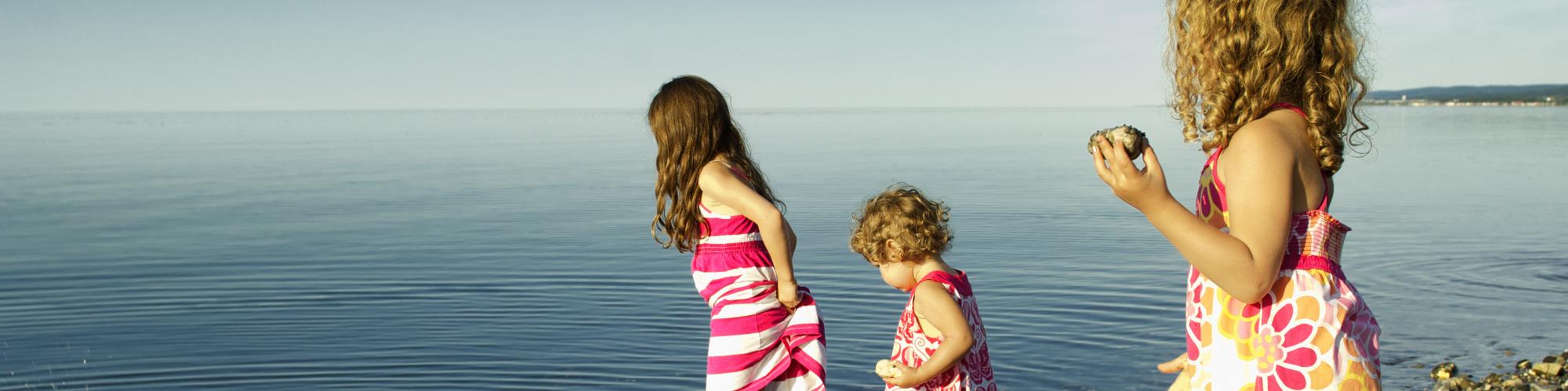 3 petites filles jouant sur la page, près de l'eau
