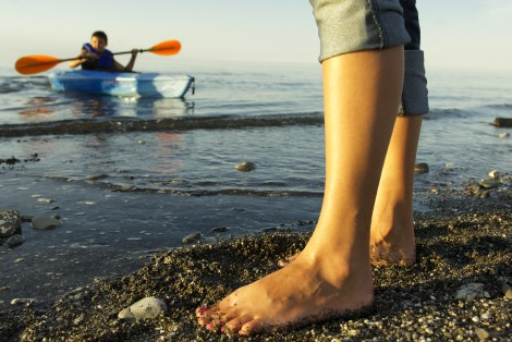 Bare feet on the beach, young boy sea kayaking