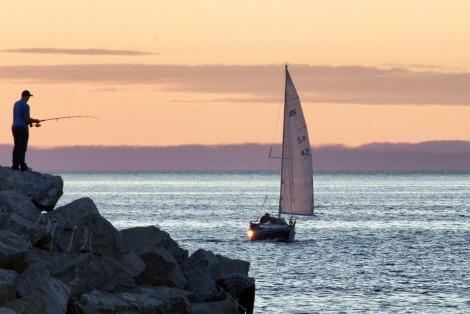 Pêcheur sur le bord de la mer, voilier à l'horizon