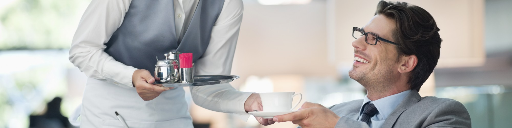 Waitress serving coffee to a business man