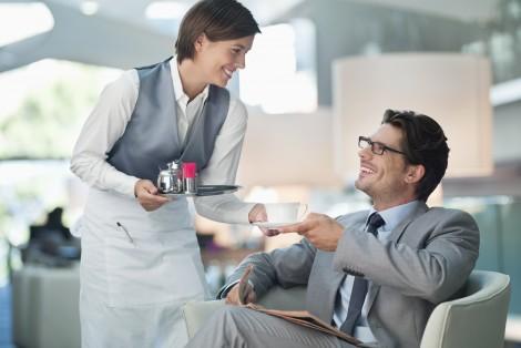 Serveuse offrant un café à un homme d'affaires