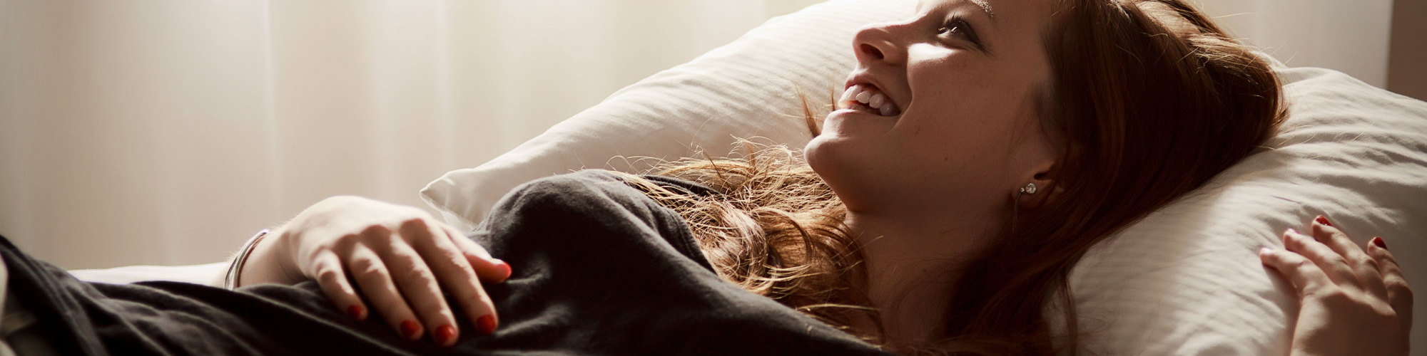 Young woman stretched out on a bed