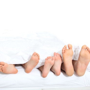 Family's feet in a white bed