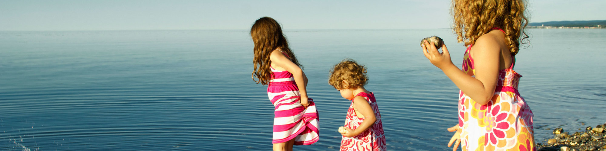 3 little girls playing in the water on the beach