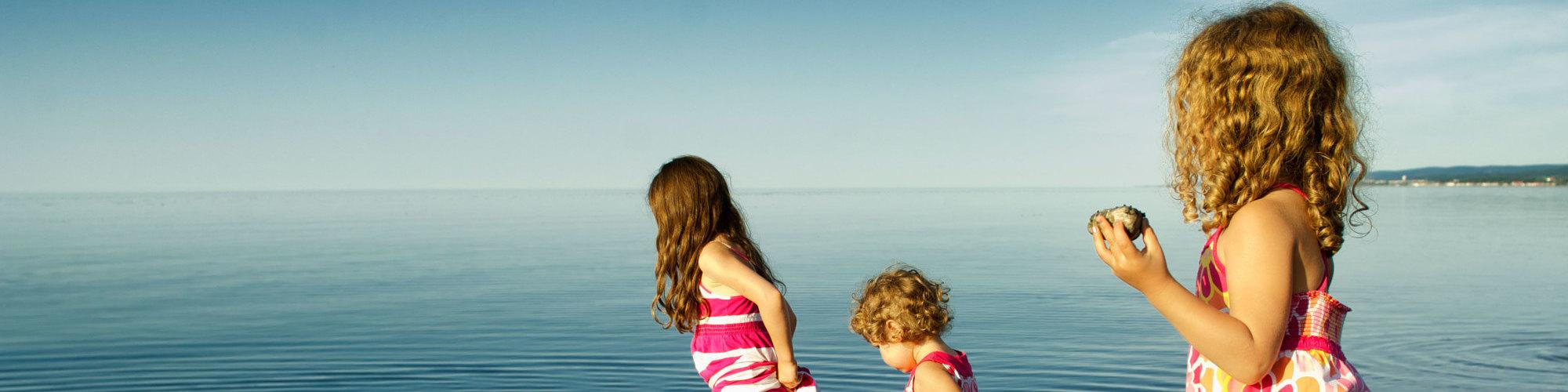 3 petites filles qui jouent dans l'eau, sur la plage