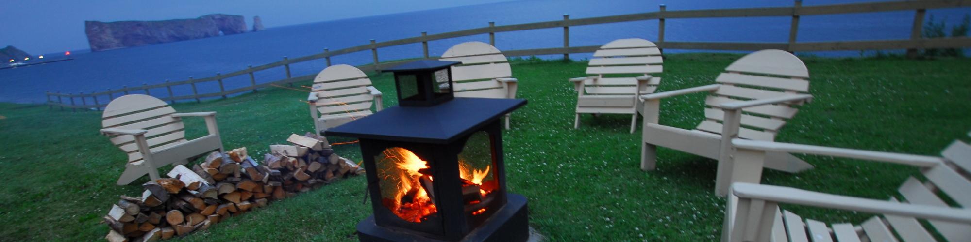 Chaises autour d'un feu, vue sur la mer et sur le rocher Percé