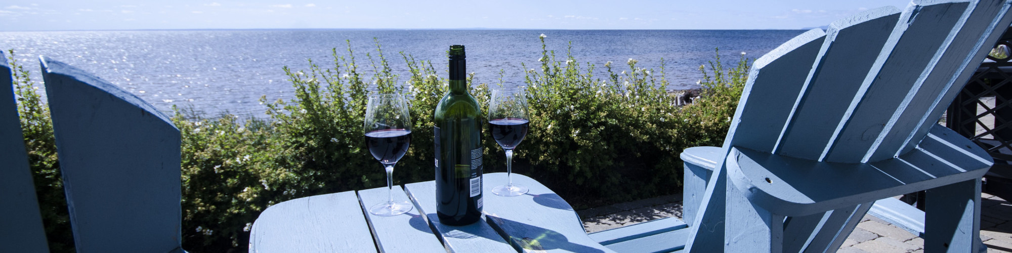 2 chairs on a terrace, sea view, wine glasses