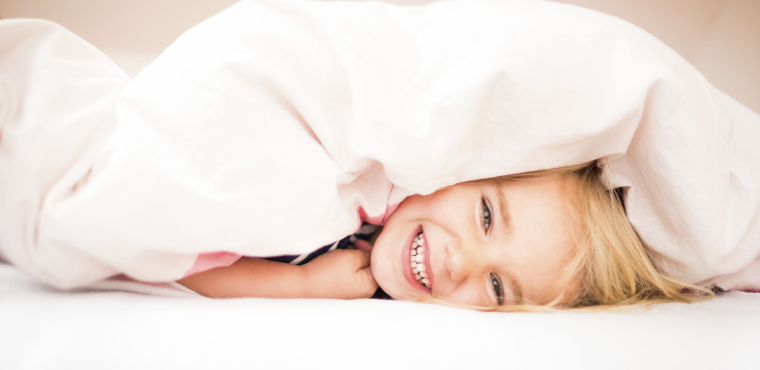 Child hiding under the covers