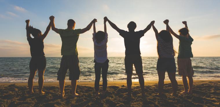 Groupe de personnes main dans la main sur la plage