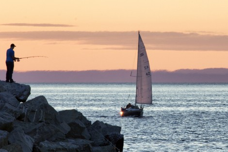 Fisherman by the sea, sailboat on the horizon