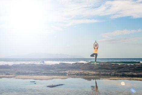 Femme qui fait du yoga en bord de mer